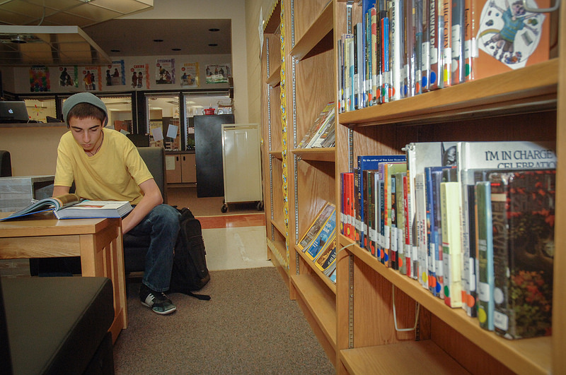 Student sitting in a library reading a book